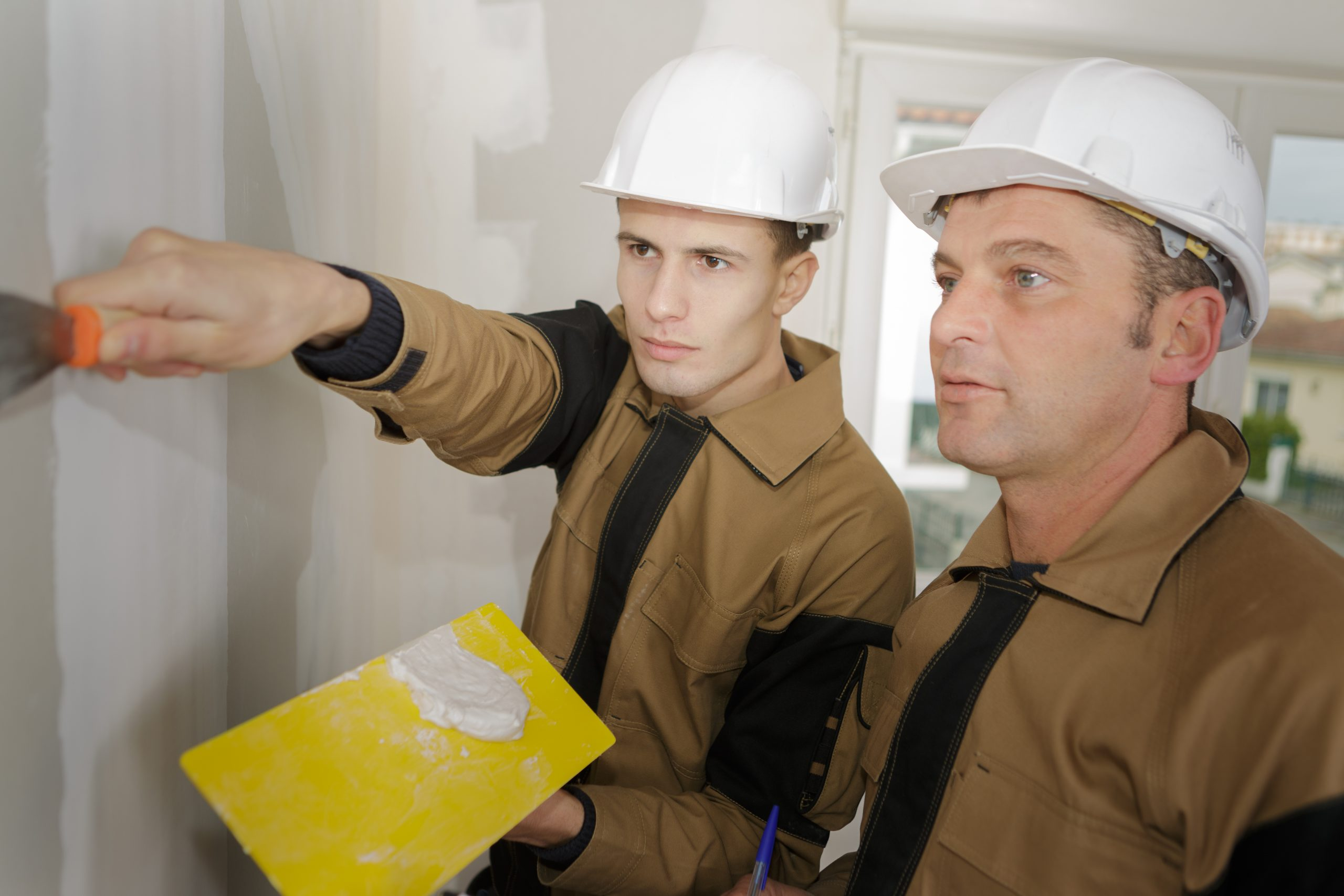 supervisor overseeing apprentice using filler on plasterboard